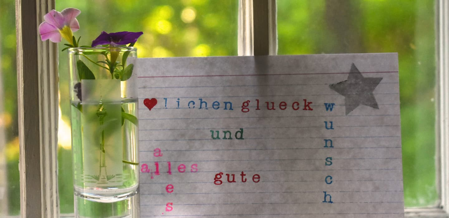 Vase and index card with German text in front of window