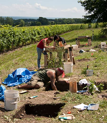 People excavating archaeological site with fields in the background